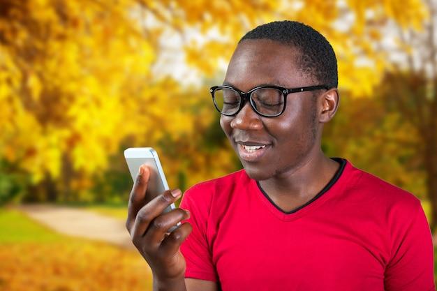 スマートフォンを使用して笑顔若いアフリカ人の肖像画