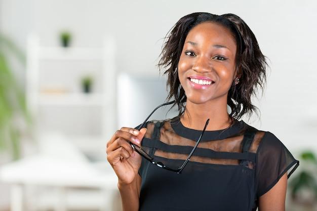 彼女の眼鏡を押しながら笑みを浮かべて若いアフリカ人女性