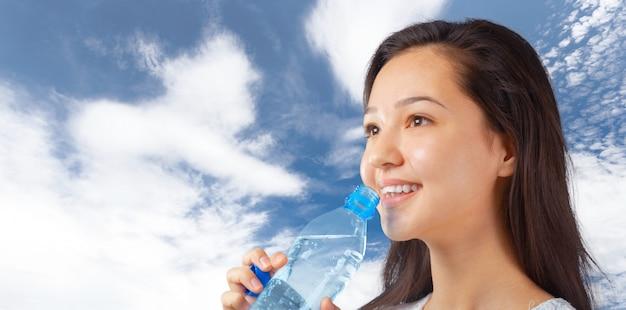 水のボトルを保持している美しい笑顔の若い女性