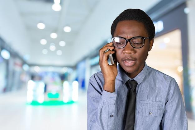 携帯電話で幸せな若いアフリカ人の肖像画