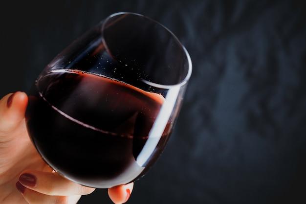 Рука держит бокал красного вина