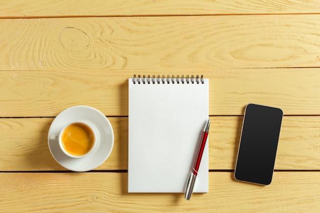 Вид сверху. кофейная чашка с кофе. перо положить на пустой блокнот.