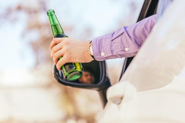 Мужчина пьет алкоголь во время вождения автомобиля