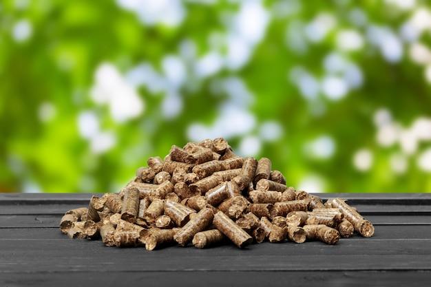 緑の背景に木質ペレット。バイオ燃料。
