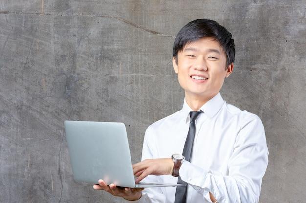 ラップトップを保持している若い笑顔のアジア系のビジネスマン