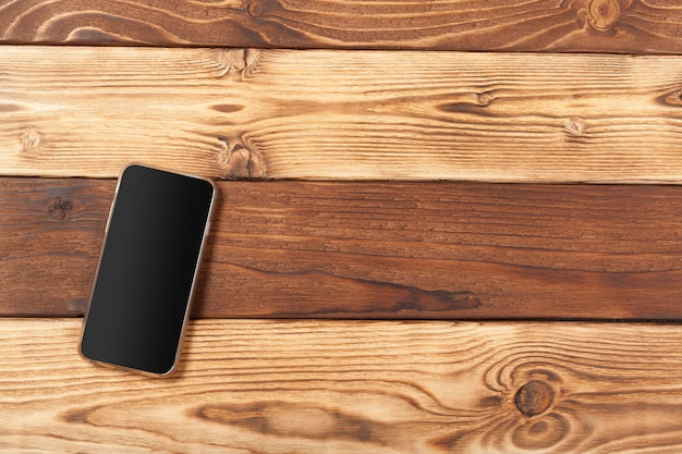Пустой экран смартфона на деревянном фоне