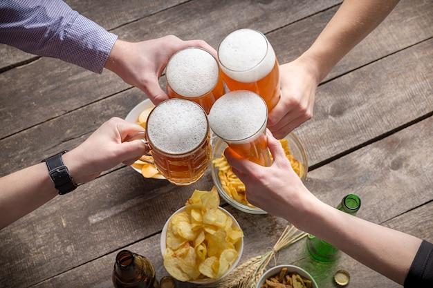 Человеческие руки и бокалы пива