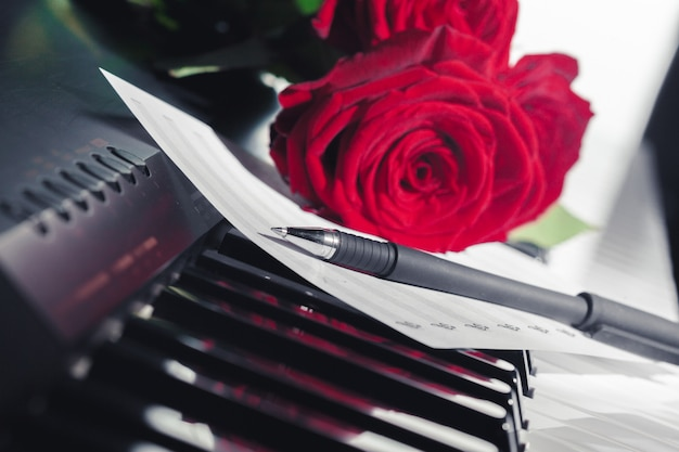 ピアノの鍵盤に赤いバラ