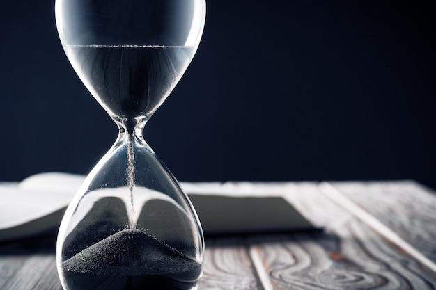Закрытые песочные часы или песочные часы на поверхности книги