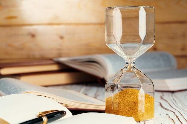 Песочные часы с песком крупным планом на деревянной поверхности