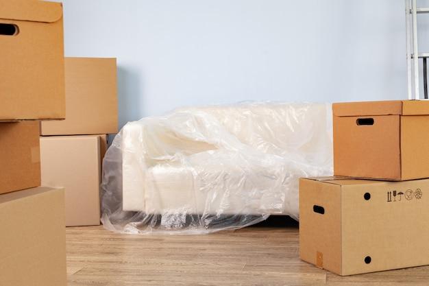 Упакованные предметы домашнего обихода в ящики и упакованный диван для переезда