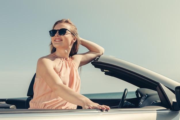 Молодая женщина водит машину на пляже