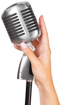 歌のための大きなレトロなマイクを保持している女性