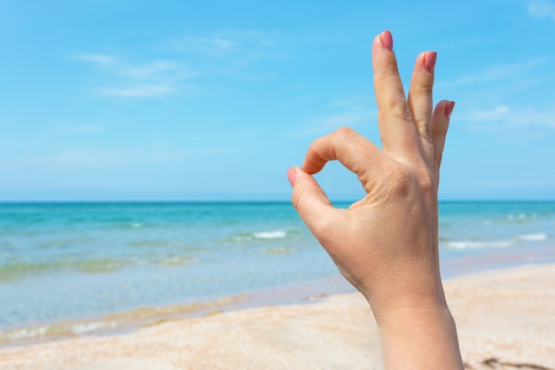 Знак рукой над голубым морем и небом поверхность, летние путешествия, отпуск концепции отдыха поверхности