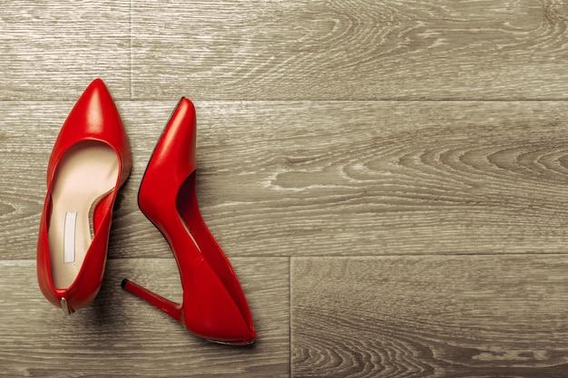 木製のテーブルに赤い女性靴