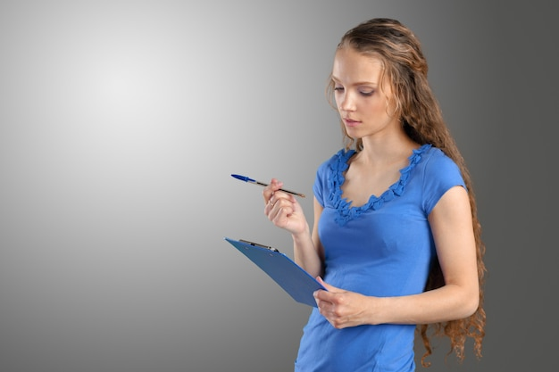 Счастливая усмехаясь молодая красивая бизнес-леди с доской сзажимом для бумаги