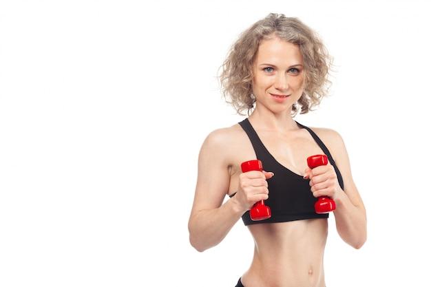 Фитнес женщина работает с гантелями