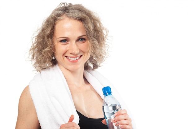 Портрет счастливой улыбкой молодой женщины в спортивной одежде с бутылкой воды