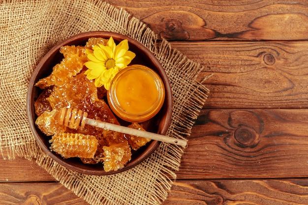 ヴィンテージの木製の背景に蜂蜜ディッパーと瓶の蜂蜜