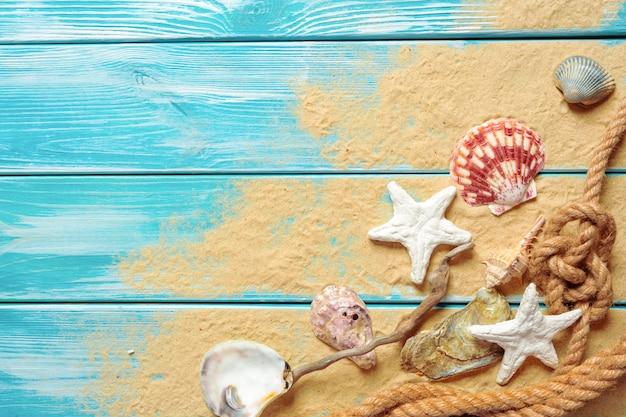 青い木製の背景に海の砂の上の多くの異なる貝殻と海ロープ。上面図