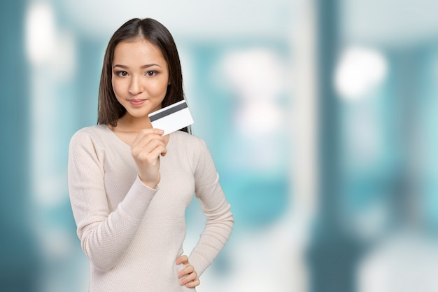 幸せな笑みを浮かべて示すクレジットカードを保持しているカジュアルなビジネス女性
