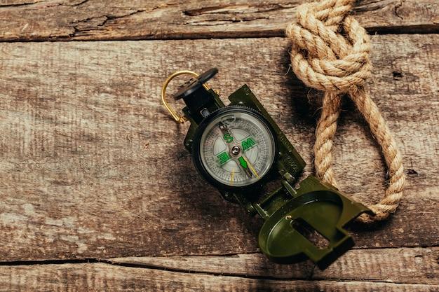 Корабельные канаты и компас на деревянном фоне