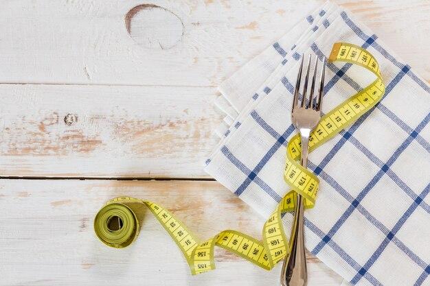 Измерительная лента на деревянном фоне. концепция диеты