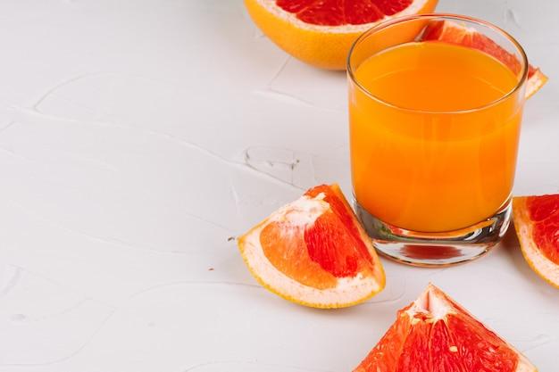 Стакан апельсинового сока и апельсиновые дольки