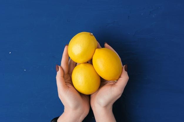 クラシックブルーに対してレモンを持つ女性の手