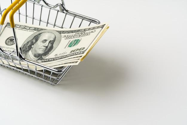 アメリカのドルの中でおもちゃのショッピングカート。購買力と生活賃金の概念