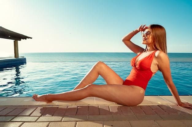 Модная женщина в красном бикини сидит возле бассейна