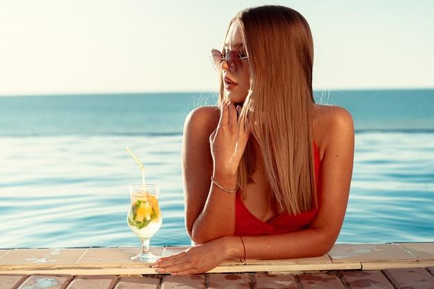カクテルを片手にプールで赤いビキニで日焼けした女性