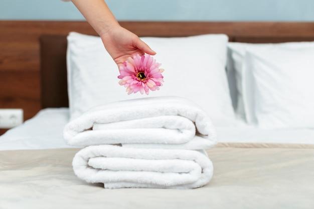 ホテルの部屋でハウスキーピング中に清潔で清潔なタオルでメイド