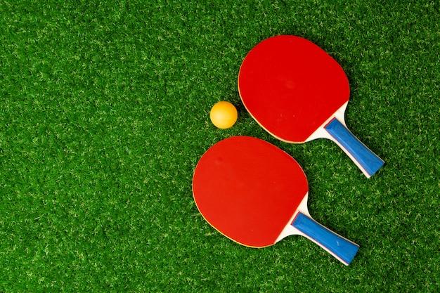 卓球ラケットと草の上のボール