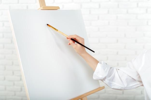 Молодая женщина-художник рисует картину в студии