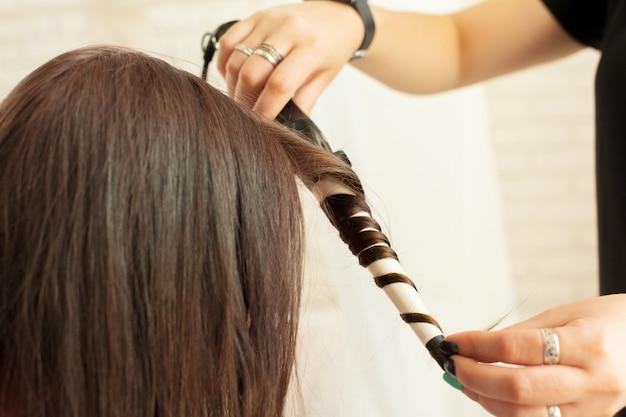 Парикмахер-парикмахер, завивающий волосы клиента в парикмахерской
