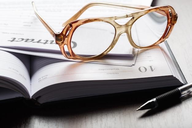 契約文書論文ビジネスコンセプトに眼鏡のショットを閉じる