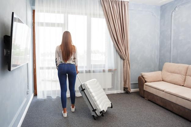 朝の時間でホテルの部屋の窓の近くに立っている女性