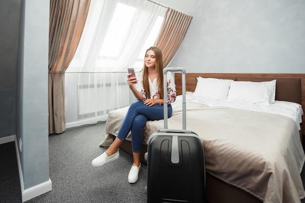 ホテルの部屋のベッドで横になっている若い女性