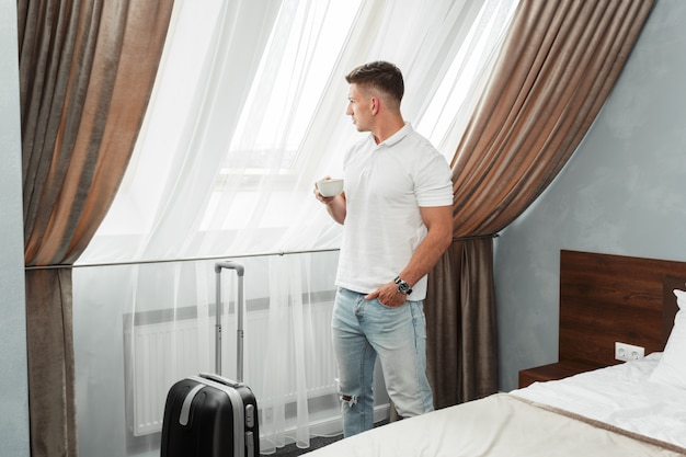 若い男のビジネス旅行者のホテルの部屋の宿泊施設