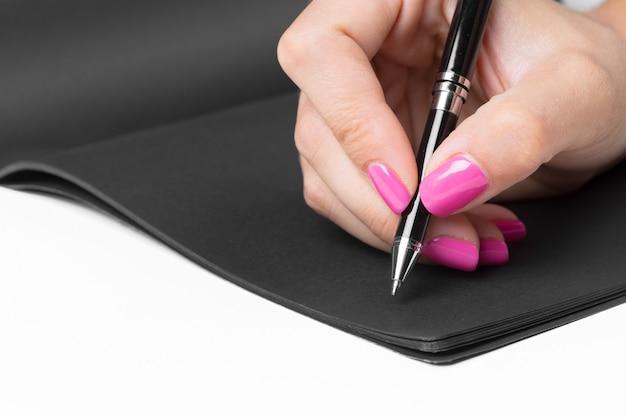 Руки бизнес-леди работая пишущ тетрадь