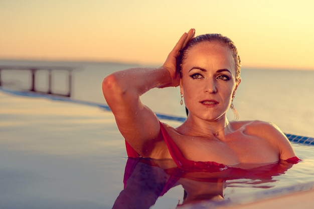 プールの水で赤いビキニの中年女性