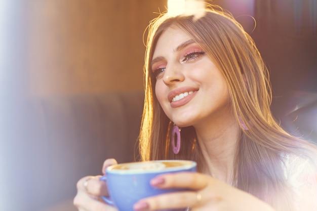 Портрет молодой женщины с чашкой кофе и глядя в окно