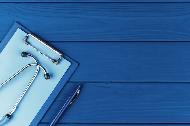 Медицинский стетоскоп на классическом синем фоне вид сверху