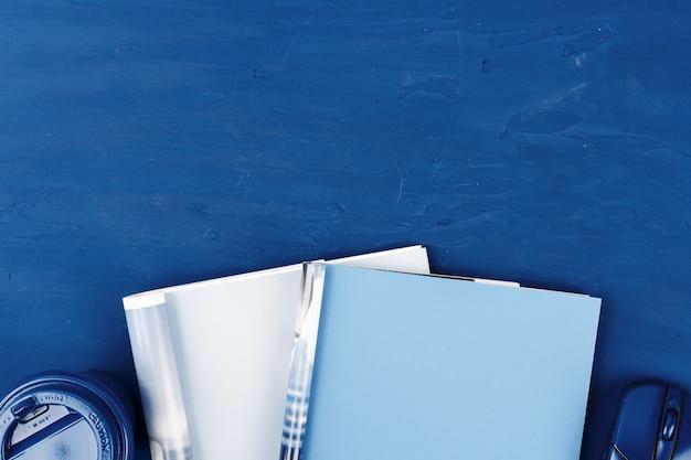 古典的な青の背景にコピースペースで開いている雑誌のページのトップビュー