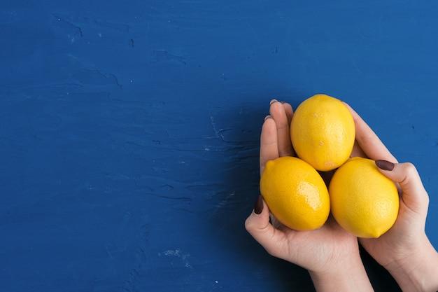 古典的な青い背景、トップビューに対してレモンを持つ女性の手