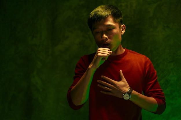中国人の男が彼の口を覆って咳をします。コロナウイルスの大流行の概念