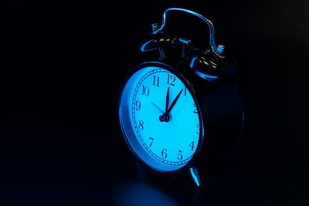 目覚まし時計は黒の背景にクローズアップ
