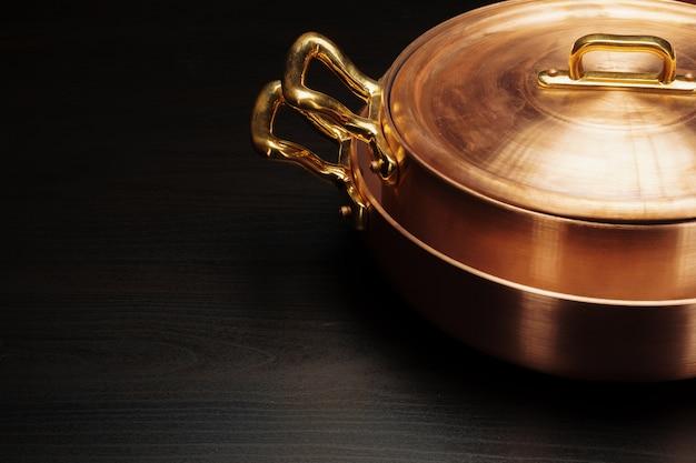 暗い背景上の光沢のあるビンテージ銅調理器具