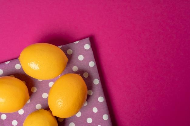 明るいピンクの紙の背景に熟したレモン